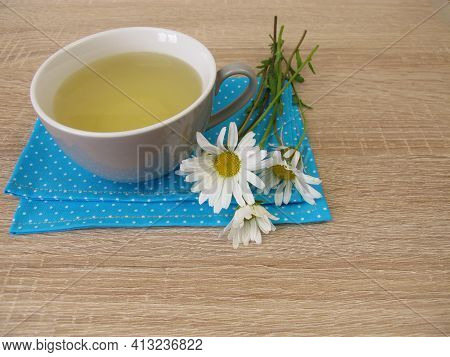 A Cup Of Herbal Tea With Flowers From The Ox-eye Daisy
