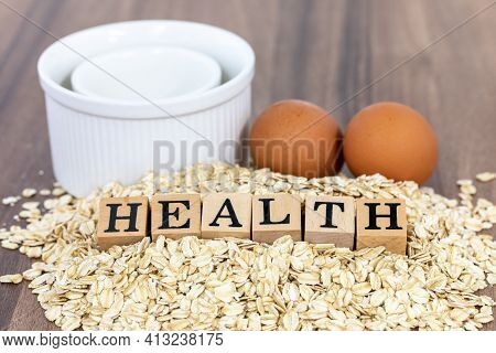 Wood Block On Oatmeal Beside With White Ramekins And Eggs On Wooden Tabletop