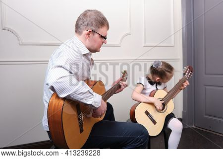 Little Girl And Her Father Are Playing Guitar. Learning To Play The Guitar. Music Education And Extr
