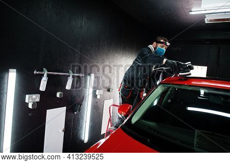 Car Detailing Concept. Man In Face Mask With Orbital Polisher In Repair Shop Polishing Roof Of Orang