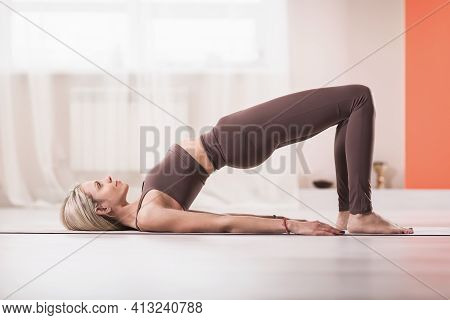 Attractive Blonde Woman In Sports Beige Leggings And Tank Top, Practicing Yoga, Doing Glute Bridge E