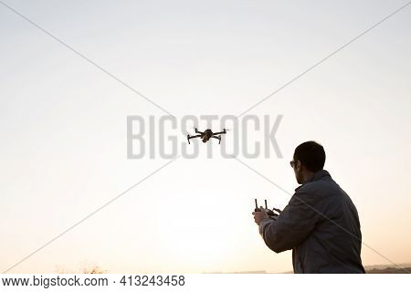 A Man Launches A Drone Into The Sky. Drone Operator With Setting Sun.
