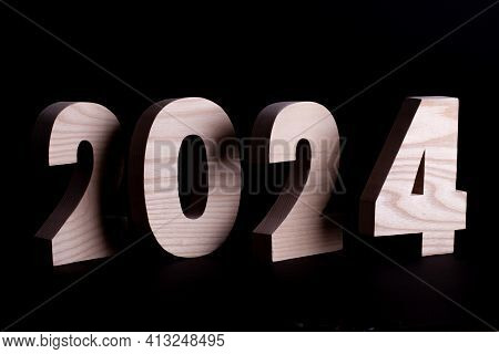 2024 Year Large Wooden Numbers Overlapping. Hardwood Characters On A Black Background