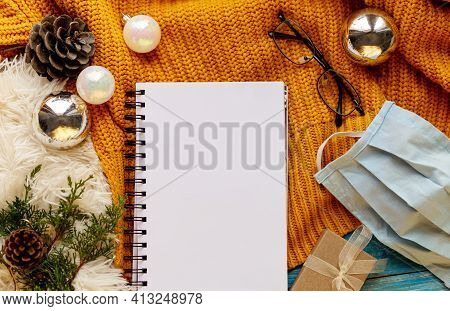 Winter Or Autumn Cozy Flat Lay Composition. Warm Knitted Sweater, Xmas Toys, Medical Mask, Cup And B