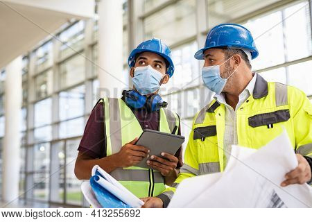 Mixed race architect and technician at construction site reviewing blueprints while wearing surgical face mask and hardhat. Team of specialists construction worker with face mask using digital tablet.