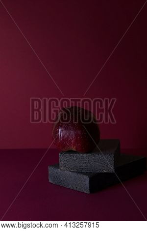 A Red Apple On A Maroon Background With Space For Text Is A Concept Of Simplicity And Elegance.geome