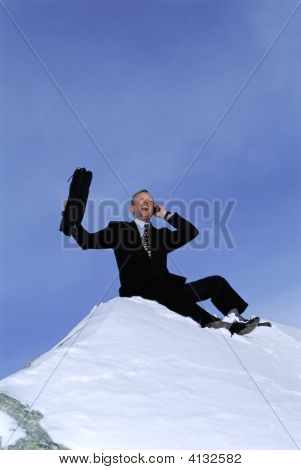 Businessman Outdoors On Snowy Mountain Using Cellular Phone And Yelling