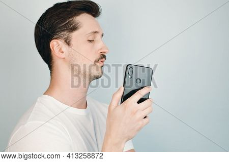 Young Man Watches His Phone And Secretly Takes Photo. Portrait Of Mustachioed Man Illegally Taking P