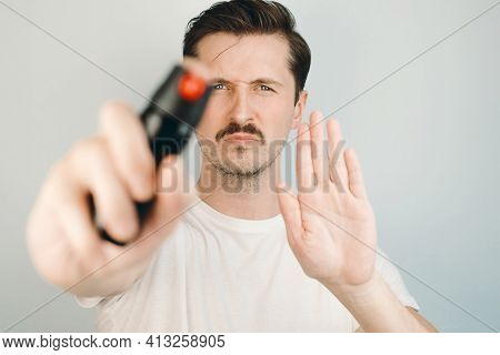 Man Holding Pepper Spray And Showing Warning Gesture. Self Defense Concept. Close-up, Selective Focu