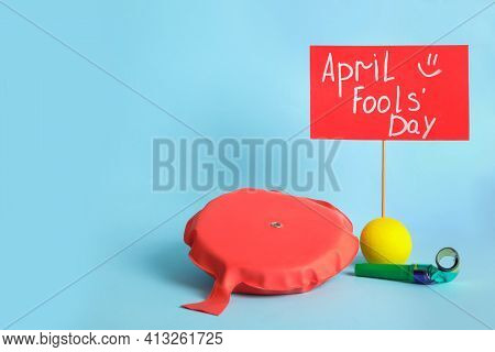 Sign With Phrase Happy Fools' Day And Clown's Accessories On Light Blue Background, Space For Text