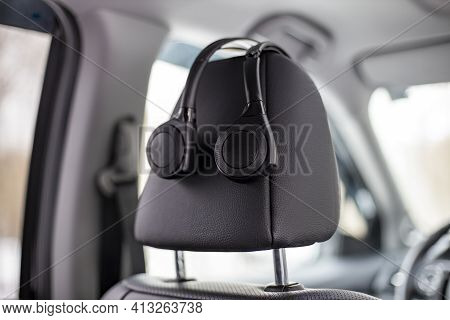 On-ear Headphones Hang On The Headrest In The Car. Technology Personal Multimedia System In A Modern