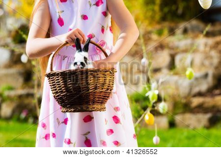 Little girl on Easter egg hunt in the spring, an Easter bunny is sitting in a basket