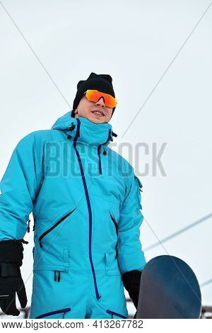 Male Snowboarder In A Blue Suit Walking On The Snowy Hill With Snowboard, Skiing And Snowboarding Co