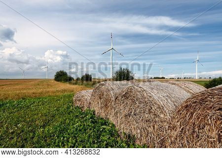 Wind turbines farm and straw bales after harvest