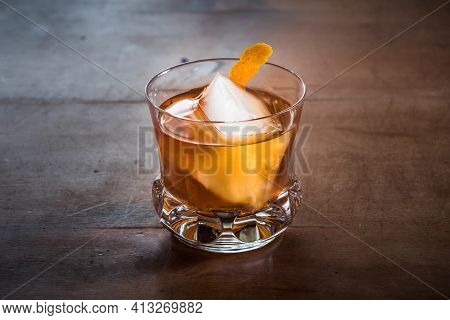 Old Fashioned Cocktail With Whiskey On A Wood Table With Orange Twist In An Elegant, Retro Crystal G