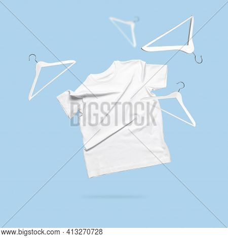 White Flying Cotton T-shirt White Wooden Hangers On Blue Background. Clean White T-shirt For Women O