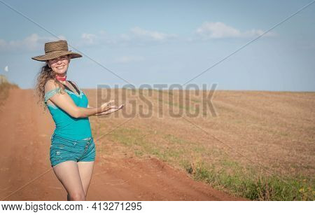 Brazilian Woman Wearing A Hat Showing A Planting Field.