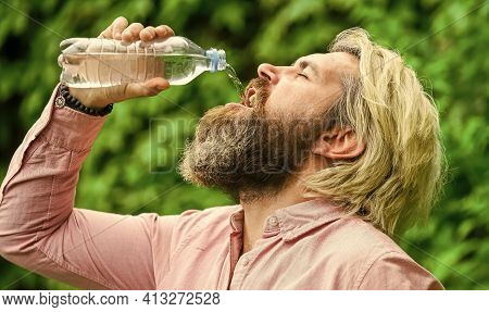 Water Balance. Man Bearded Tourist Drinking Water Plastic Bottle Nature Background. Thirsty Guy Drin