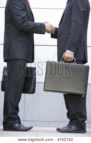 Two Businessmen Holding Briefcases Outdoors Shaking Hands