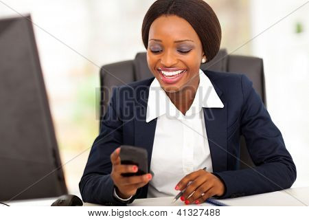 happy african american businesswoman reading sms in office