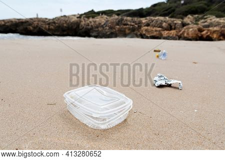 closeup of a used plastic container thrown on the wet sand of a beach, next to some other garbage, such as a piece of aluminum foil or a used plastic bottle