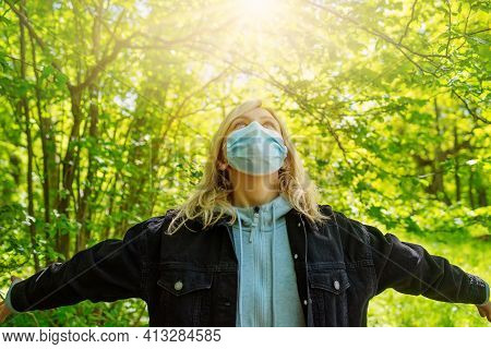 Young Woman In Medical Face Protection Mask Outdoors In Nature. Girl Hoping For The End To The Pande