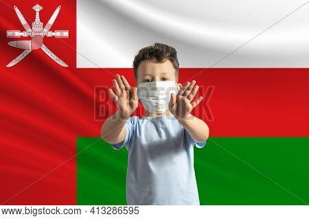 Little White Boy In A Protective Mask On The Background Of The Flag Of Oman. Makes A Stop Sign With