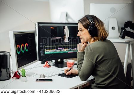 Profile View Of Female Designer Sitting, Editing Video On A Computer At Her Workplace. Modern Busine