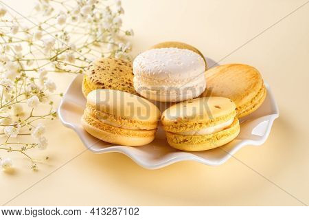 Yellow Macaroons On A White Elegant Saucer Against Pastel Yellow Background. Sweet Breakfast With De