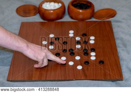 A Man Plays The Board Game Go. Traditional Chinese Game Of Go. A Brutal Male Hand Holds A Token From