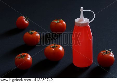 Fresh Red Tomatoes Selected For Making Ketchup Lie On A Dark Surface Next To An Empty Plastic Bottle