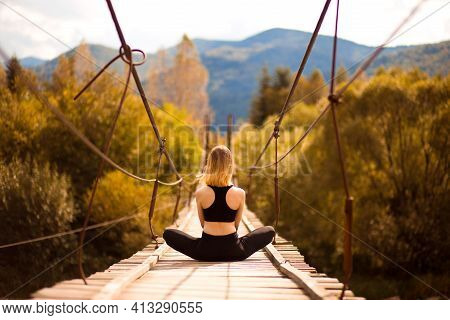 Back View Of Young Calm Girl Practicing Yoga Meditation Sitting In Lotus Pose On Bridge Over Mountai