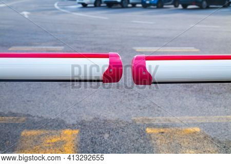 Closed Barrier On Carpark. Two White And Red Staves And Asphalt With White And Yellow Road Markings.