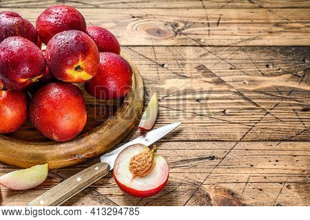 Red Nectarines On A Wooden Tray And Half A Nectarine. Wooden Background. Top View. Copy Space