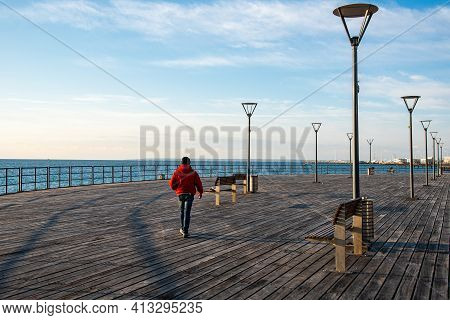 Unrecognized Person Dressed In Red Walking On Wooden Pier At Sea. Limassol Cyprus
