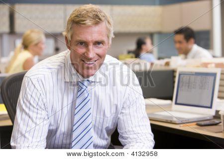 Uomo d'affari nel cubicolo sorridente