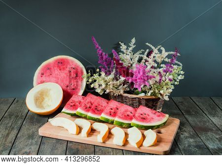 Slices Of Watermelon And Melon, Half Of Watermelon And Melon And Wicker Basket With Astilbe And Hydr