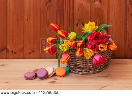 Fresh Tulips In Wicker Basket And Colorful Macaroons On Wooden Table. Selective Focus. View With Cop
