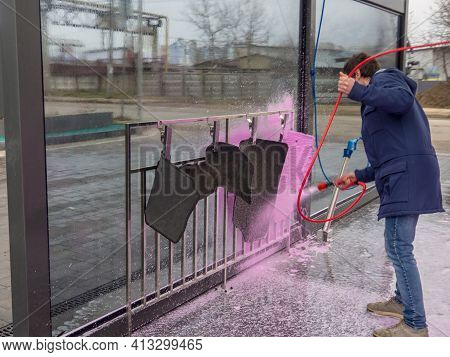 A Man Covers Auto Mats With Pink Foam At A Self-service Car Wash. Car Wash With A Spray Of Magenta S
