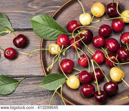 Sweet Cherries In A Plate. Ripe Sweet Sweet Cherries In A Plate On A Wooden Background