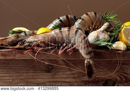 Prawns With Lemon, Rosemary And Garlic On A Old Wooden Table. Copy Space.