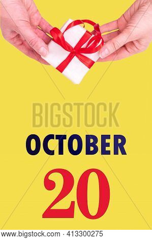 October 20th. Festive Vertical Calendar With Hands Holding White Gift Box With Red Ribbon And Calend