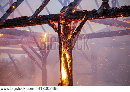 Burned Down Wooden Barn With Fire And Sparks Still Blazing. Charred Roof Truss And Wooden Posts. Bur