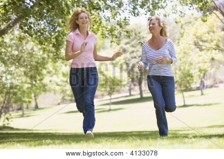 Two Women Running In Park And Smiling