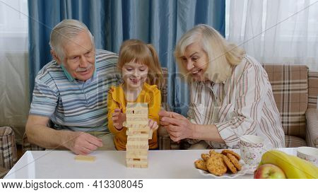 Senior Couple Grandparents With Child Granddaughter Spending Time Home Together, Sitting, Playing Ga