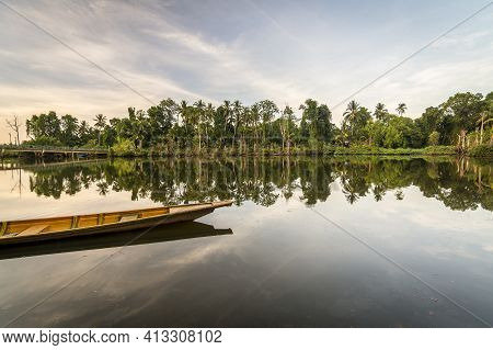 Wooden Canoe In A Quiet River At Sunrise