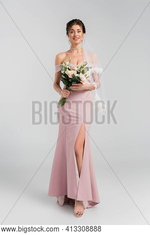 Full Length View Of Smiling Fiancee In Pink Dress Posing With Bouquet On Grey.