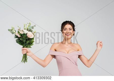 Excited Fiancee Showing Triumph Gesture While Holding Wedding Bouquet Isolated On Grey.