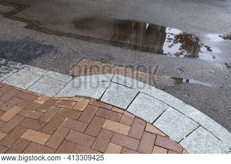 Reflections Of Sky And Urban Buildings In A Street Puddle Bordered By A Brick And Granite Curb And R