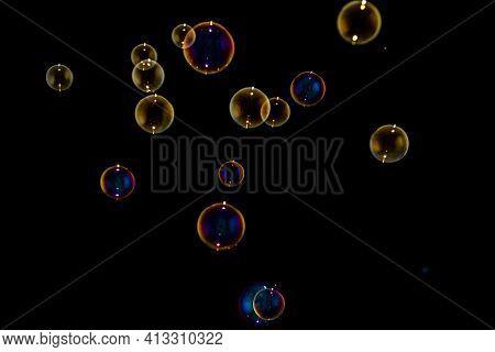 Many Rainbow Soap Water Bubbles On Isolated Dark Black Background